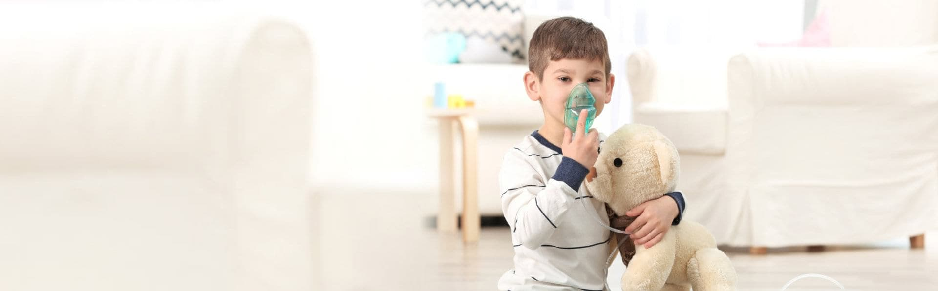 Little boy playing an oxygen mask while hugging his teddy bear